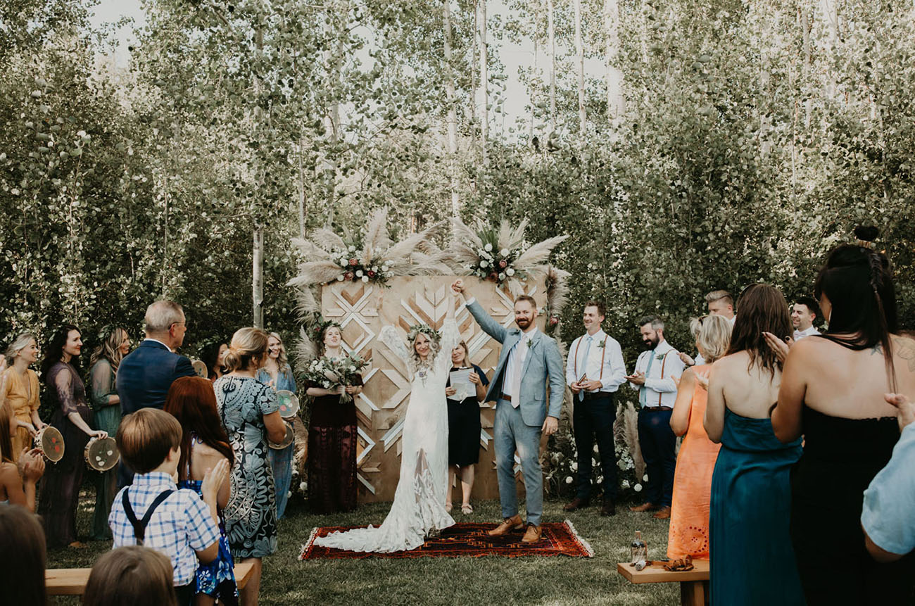 The wedding backdrop was done with catchy wooden chevron patterns and with blooms and pampas grass on top