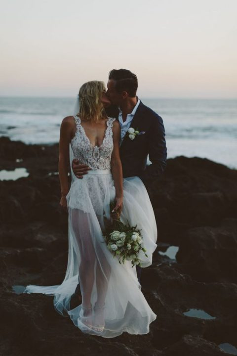 a bold modern wedding dress with a lace bodysuit with no sleeves and a sheer skirt plus a train