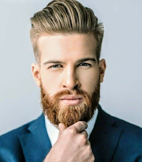 a classic longer pompadour with shorter sides and a well-groomed beard plus moustache
