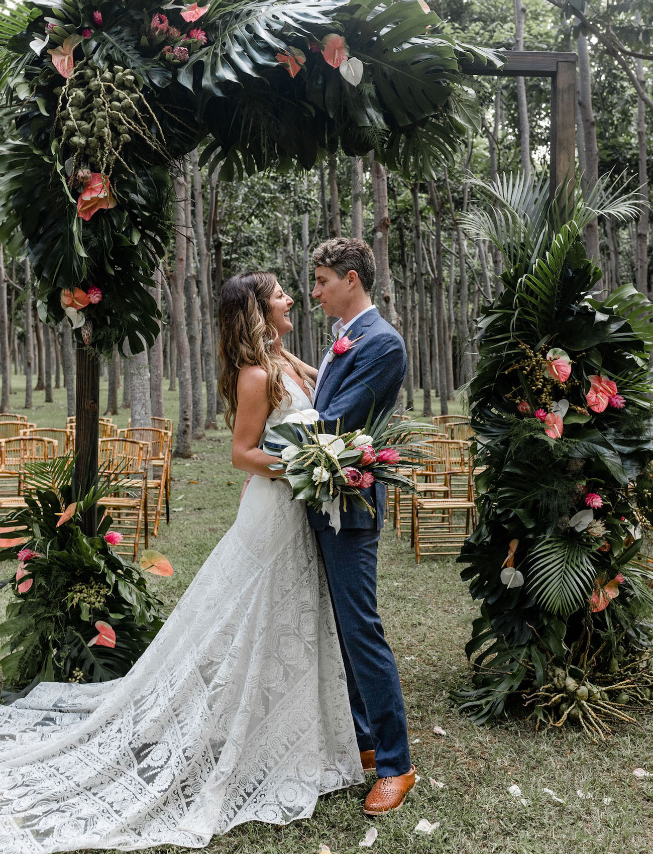 The wedding arch was done with tropical leaves and tropical pink blooms