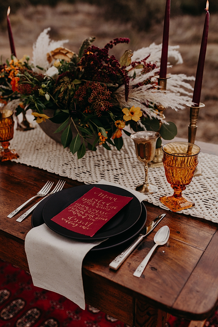 The wedding tablescape was done with a macrame table runner, black plates and chargers, burgundy candles and amber glasses