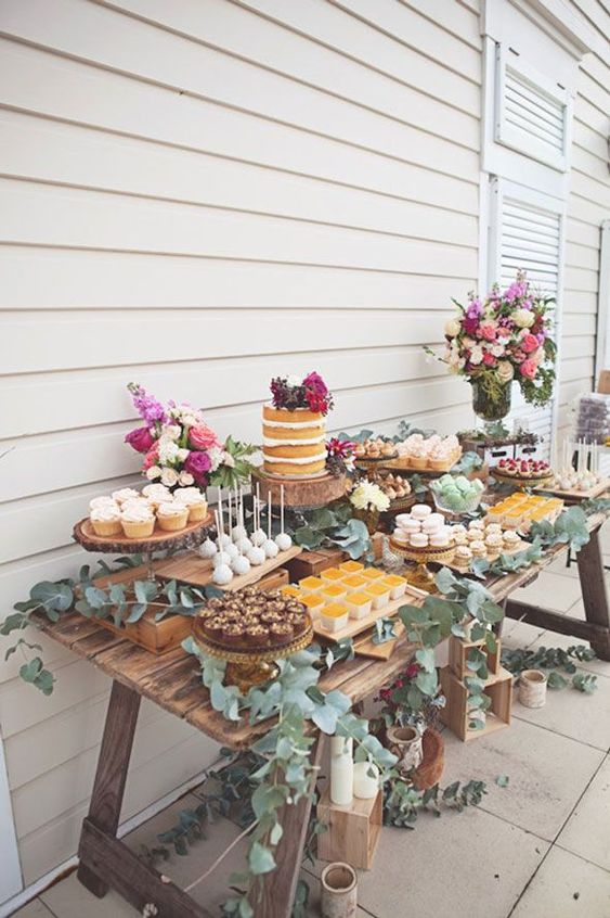 a simple rustic dessert table of wood, all covered with eucalyptus, with lots of bold blooms and desserts