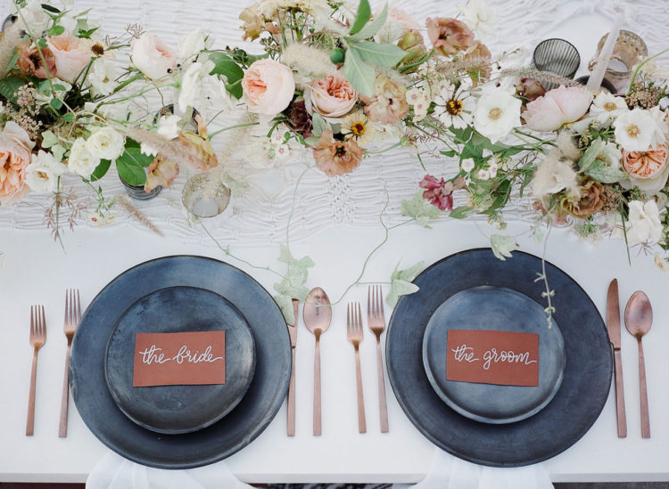 The reception table was done with matte grey plates and chargers, delicate blooms, copper cutlery