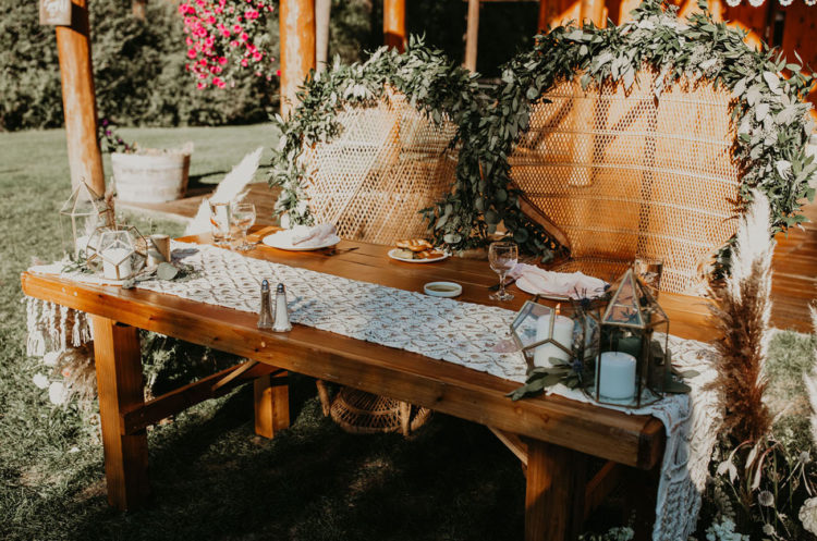 The sweetheart table was styled with a runner, some greenery, terrariums and peacock chairs with greenery