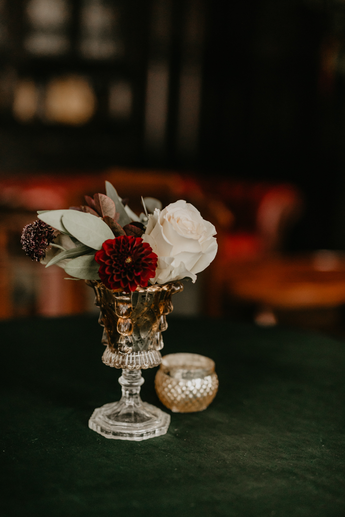 The wedding centerpieces were made of vintage glasses, red and white blooms and foliage
