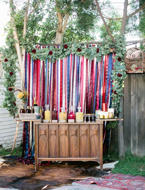 a drink station with a touch of boho - a colorful stripe backdrop and lush greenery plus a mid-century modern sideboard