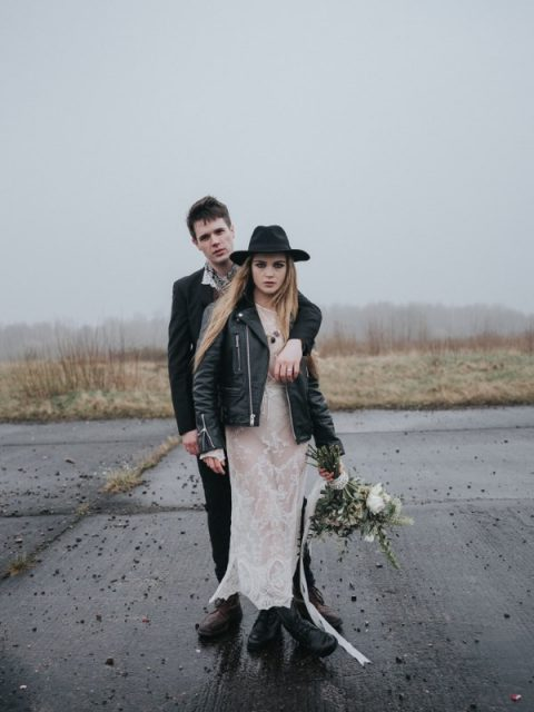 a naked lace wedding dress, a black leather jacket, black boots and a black hat for a daring rock-n-roll bride