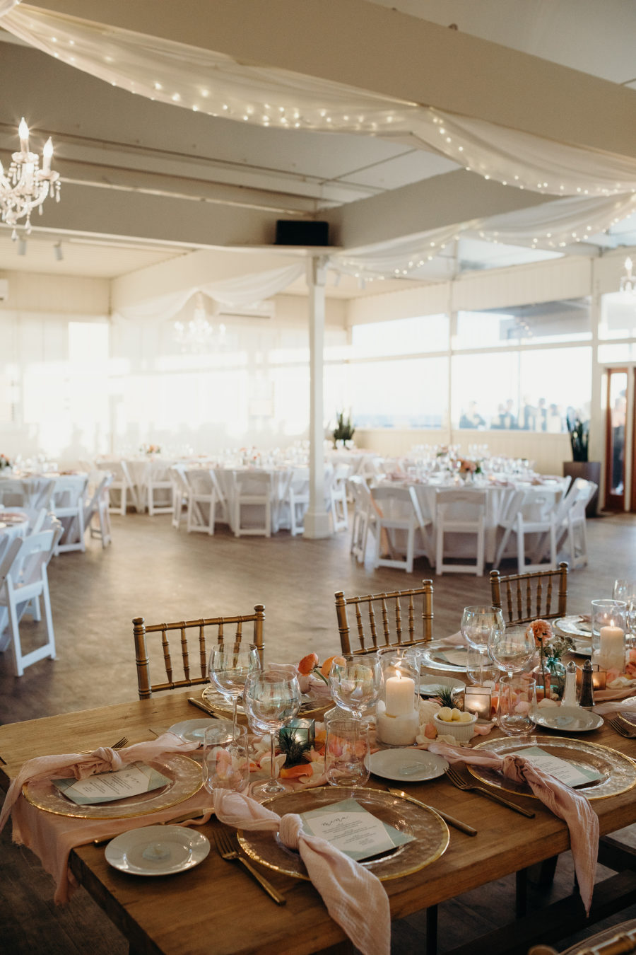 The tables were decorated with pastel blooms, gold rim chargers, blush napkins and candles