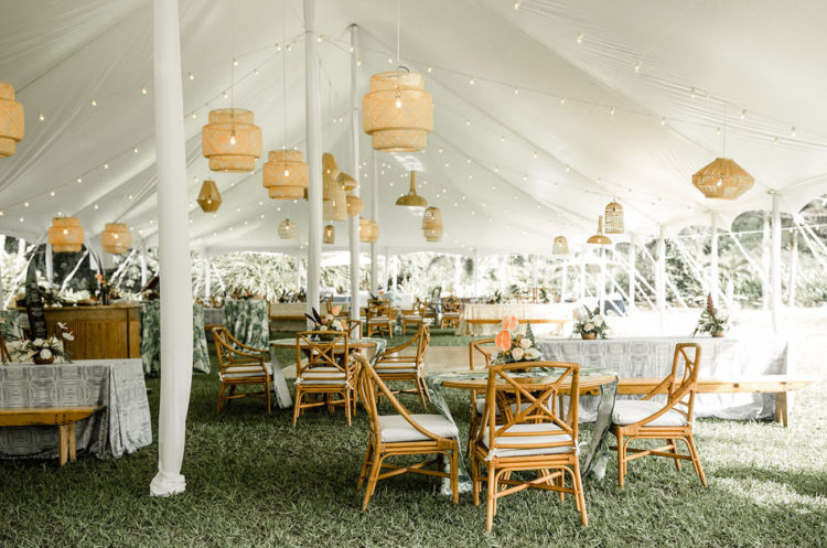 The wedding reception was done with rattan chairs and wicker lampshades and grass on the ground made it fresh