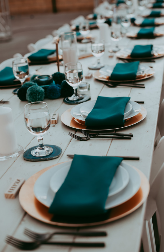 The wedding tablescapes were done with teal and turquoise, with large pompoms and napkins and nothing excessive