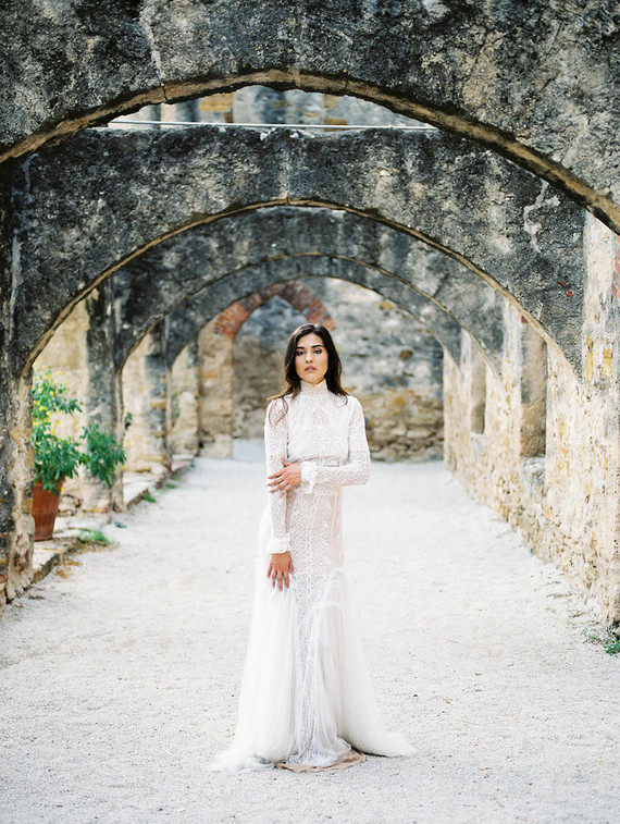 a lace sheath wedding dress with long sleeves, a turtleneck and a small train is a gorgeous idea for a modern romantic bride