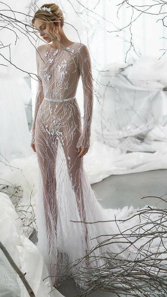 a sheer wedding dress with embroidery and lace appliques, long sleeves and a train plus a nude bodysuit underneath