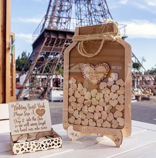 a wooden jar with little hearts and twine and a box with little hearts that can be signed by the guests