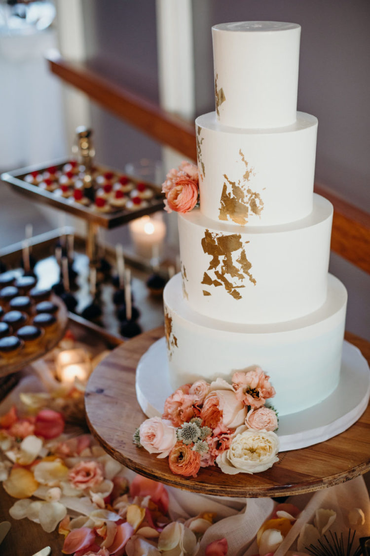 The wedding cake was a white one, with gold leaf and peachy pink blooms