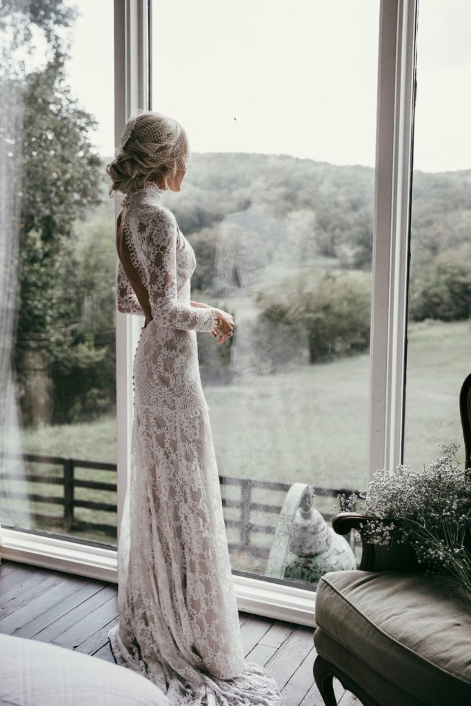 a gorgeous lace sheath wedding dress with a turtleneck and long sleeves plus a cutout back on buttons