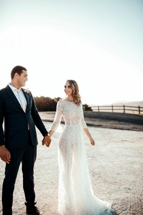 a neutral sheer wedding dress with bell sleeves, a high neckline and embellishments plus a small train
