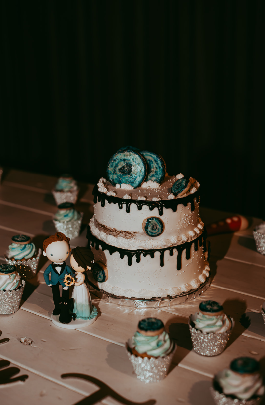The wedding cake was a white one, with chocolate drip and turquoise cookies plus matching cupcakes