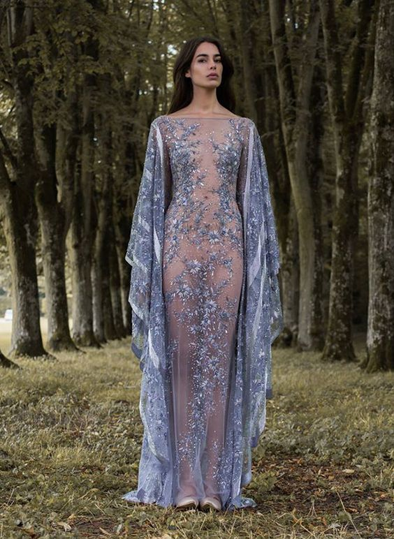 a sheer fully embellished blue wedding dress with floral embroidery, long bell sleeves, a high neckline and a nude bodysuit underneath