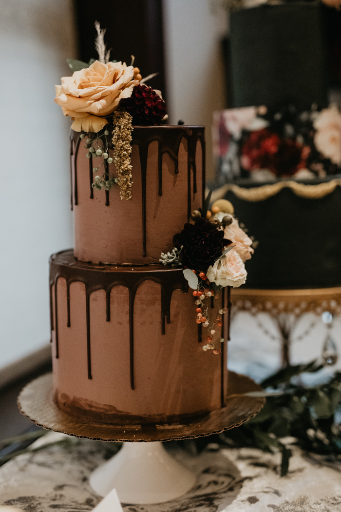 And a chocolate wedding cake with chocolate dripping and fresh blooms on top