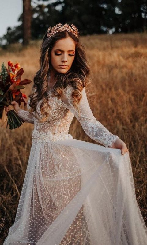 a sheer polka dot wedding dress with long sleeves, a high neckline and a cutout back is rather romantic