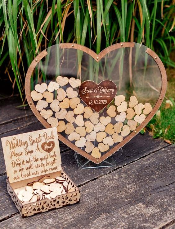 a transparent acrylic heart filled with smaller wooden hearts that are signed by the guests is a cool idea