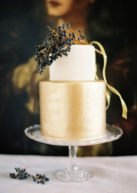 a chic color block wedding cake with a white and gold tier plus some berries on top