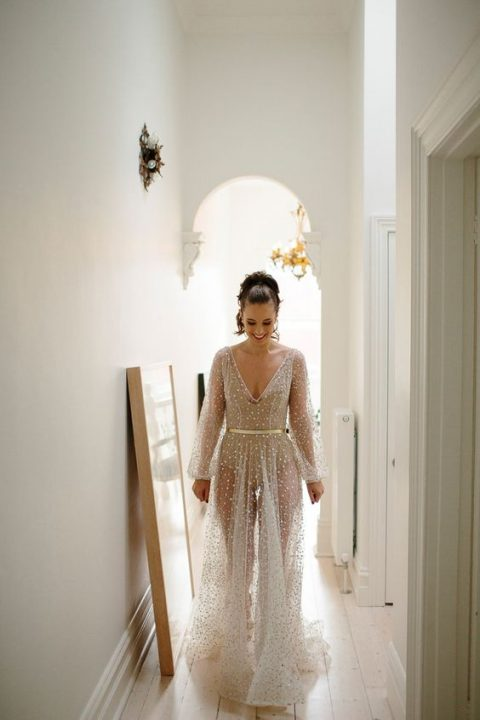 a neutral sheer wedding gown with embellishments all over it, a V-neckline, long sleeves and a bodysuit underneath