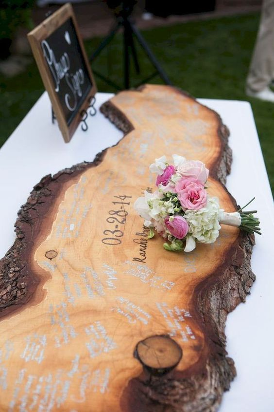 an oversized wooden slice with a living edge is a unique and bold idea of a rustic wedding guest book
