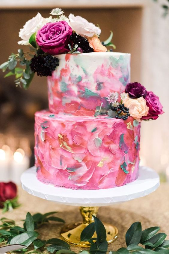 a colorful brushstroke wedding cake in pink and grey, with fresh blooms and berries on top