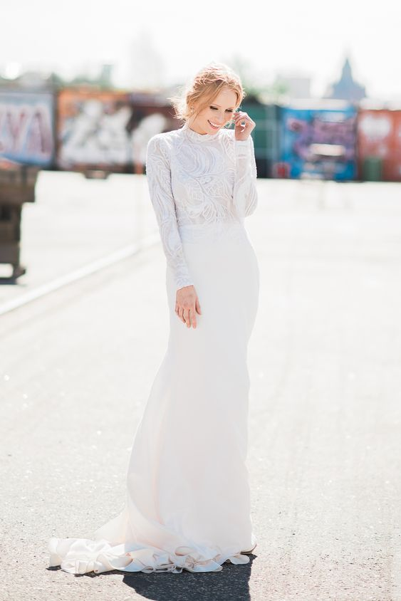 an elegant crepe wedding gown with a beaded and sequinned double layer lace top and pearl buttoned sleeves plus a train
