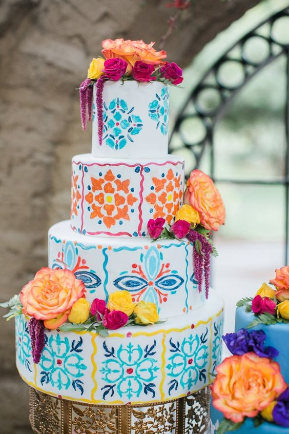 a super bright Mexican-inspired wedding cake with lots of colors and patterns plus fresh blooms