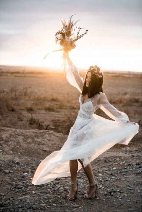 a trendy sheer pearl wedding dress with long sleeves and a lace bodysuit under it, printed shoes and a floral headpiece
