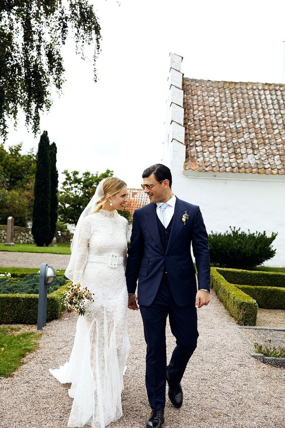 a vintage-inspired lace turtleneck sheath wedding dress with embellishments and pearls all over, long sleeves and a sash with a buckle