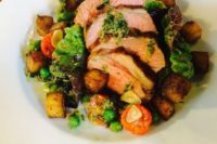 18 roasted spring rump of lamb with fresh broad bean, pea and confit tomato salad served with rosemary and garlic