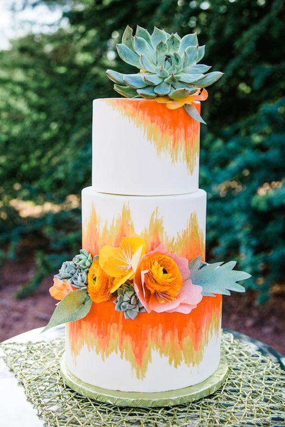 a colorful wedding cake with ombre orange and yellow patterns, succulents and fresh blooms