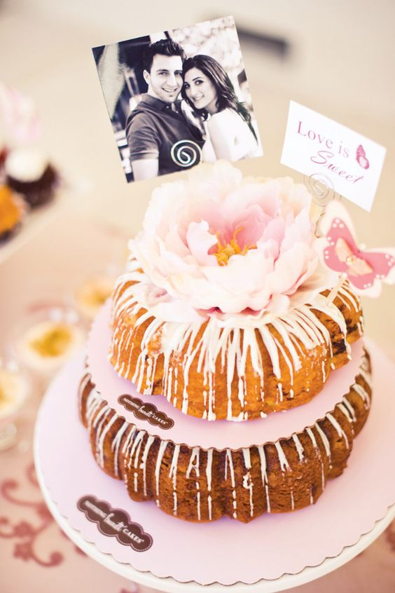 a pink glazed cake with a large fresh bloom on top, a photo and a topper for a backyard shower