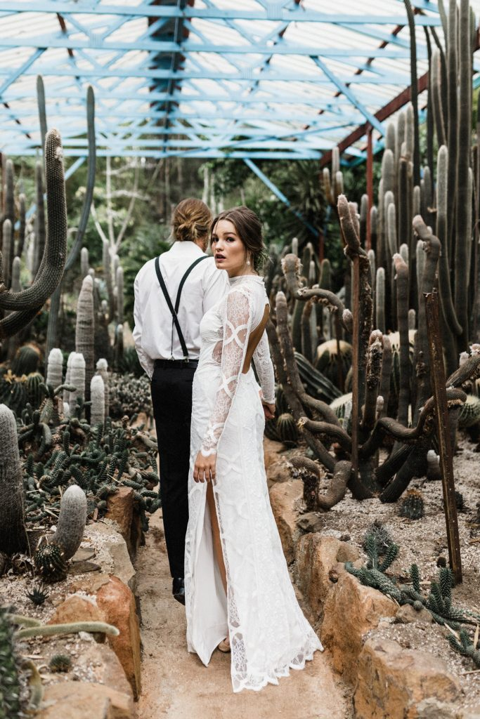 a sexy lace sheath wedding dress with a turtleneck, a side slit and a cutout back plus long sleeves