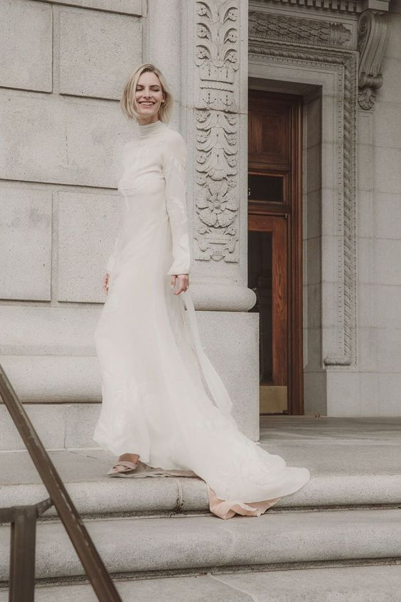 a turtleneck lace sheath wedding dress with long sleeves and a train for a modern and modest bride