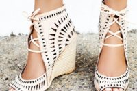 21 laser cut leather wedges featuring an open toe, adjustable lace-up detailing and a stacked wedge