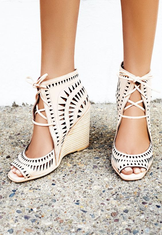 laser cut leather wedges featuring an open toe, adjustable lace-up detailing and a stacked wedge