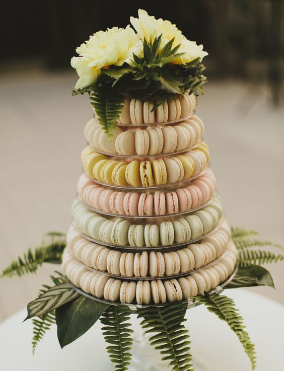 a macaron tower with creamy, blush, yellow and mint macarons plus fresh yellow blooms on top