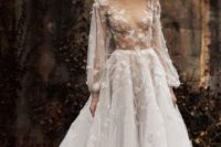 23 a romantic A-line wedding dress with a sheer bodice, long sleeves and floral appliques