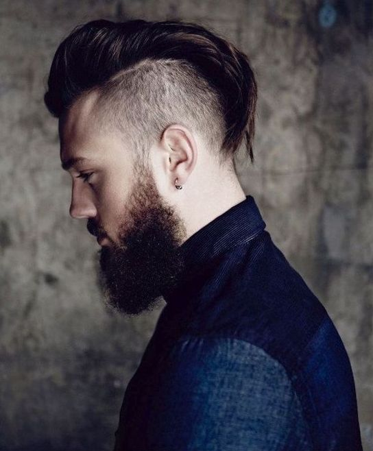 an edgy hawk haircut with longer hair on top, nearly shaved sides and a beard for a daring groom