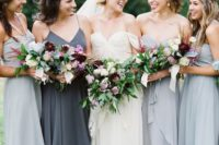 24 mismatching dove grey maxi gowns with ruffled edges and a charcoal grey spaghetti strap one for the maid of honor