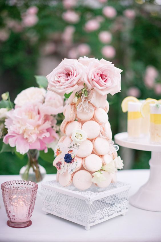 a blush mini macaron tower with fresh and sugar blooms and fresh pink roses on top