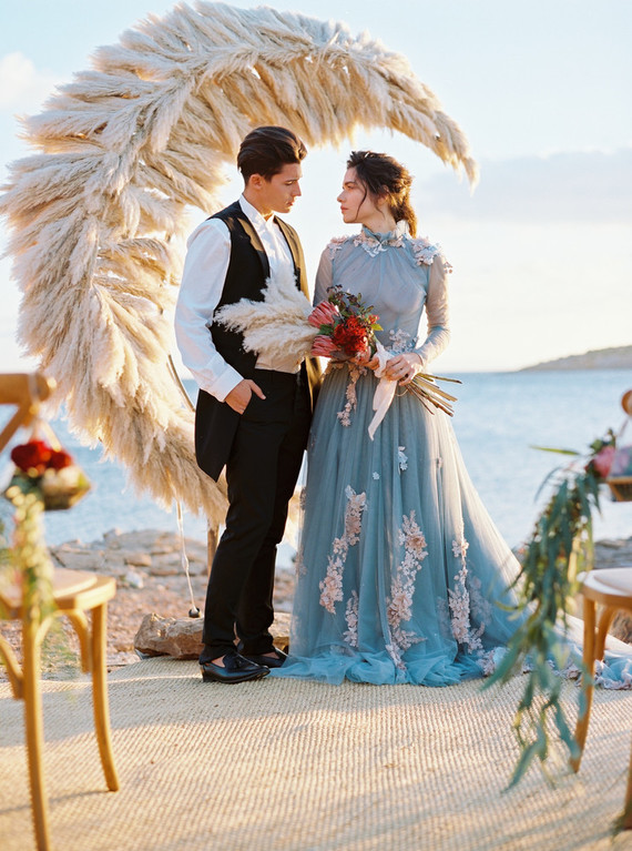 a blue wedding gown with a sheer bodice and sleeves and pink florla appliques all over the dress