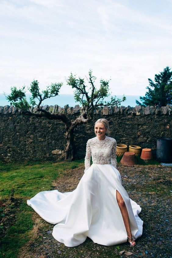 a modern wedding separate with a lace embellished turtleneck top and a plin full skirt with a front slit and a train