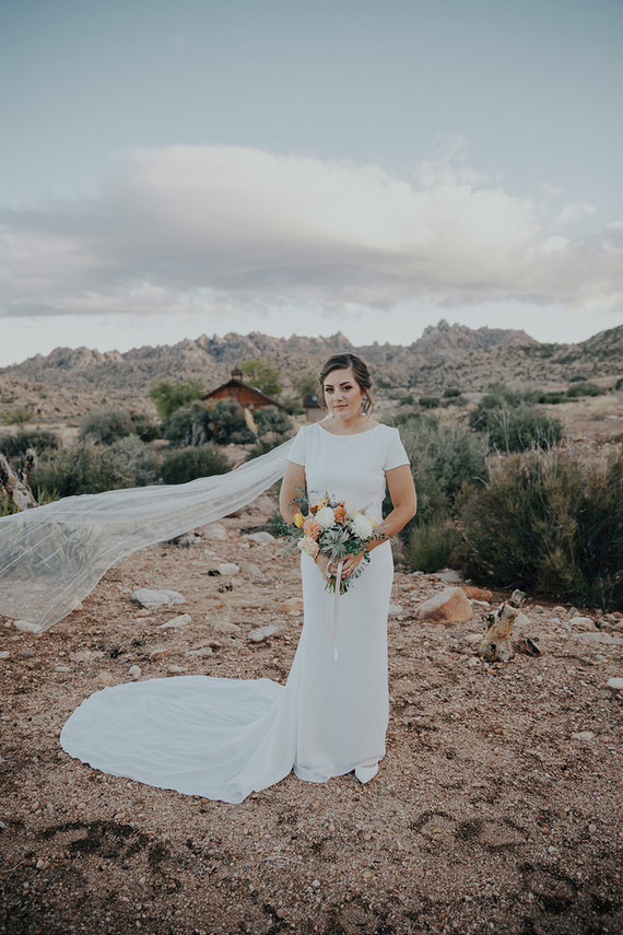 The bride was wearing a modern sheath wedding gown with short sleeves, a cutout back and a high neckline plus a long veil