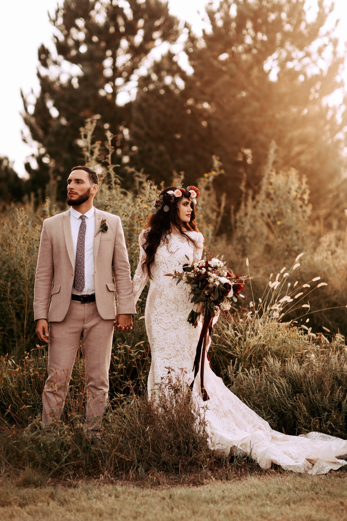 The bride was wearing an ivory lace mermaid wedding dress with a high neckline and long sleeves, the groom was wearing a tan suit with a floral tie