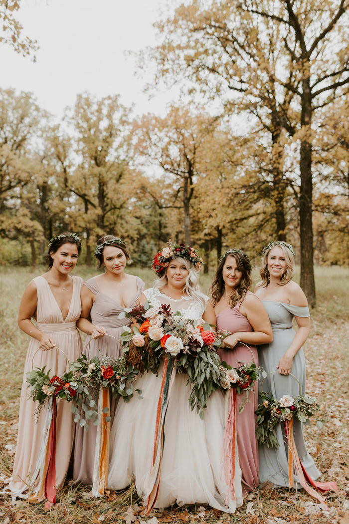 The bridesmaids were wearing mismatching pastel maxi gowns and carrying wreath bouquets with ribbons